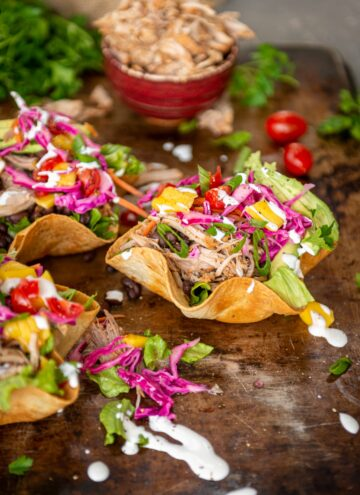 brightly colored and fresh - 3 fried tostada bowls filled with shredded carnitas, veggies, mangoes, pickled cabbage and crema