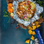 above shot of finished chilaquiles recipe in cast iron with foil for campfire or gas grill. pineapples and other topping scattered around on a blue background