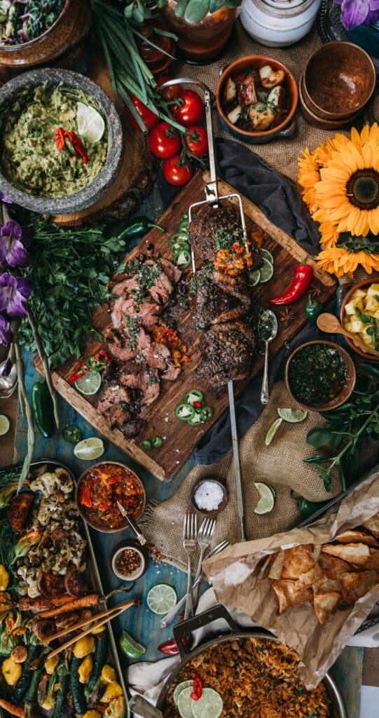 huge spread of food centered around a rotisserie beef picanha with side dishes, flowers and various sauces