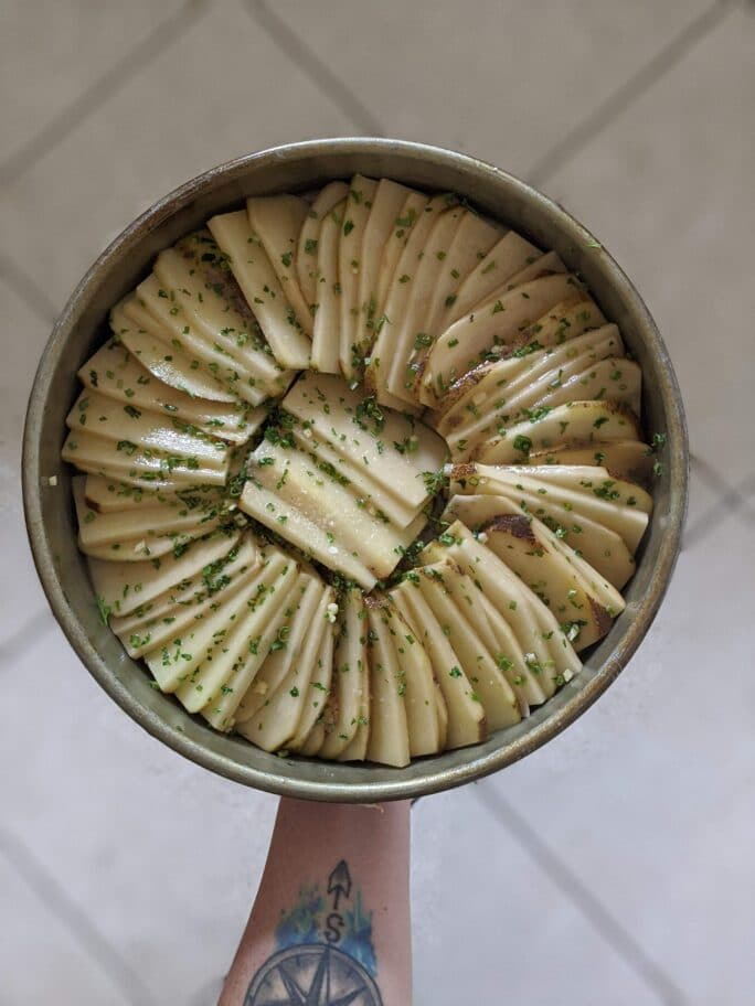 hand holding raw potatoes thinly sliced and layered in a pan ready to be baked