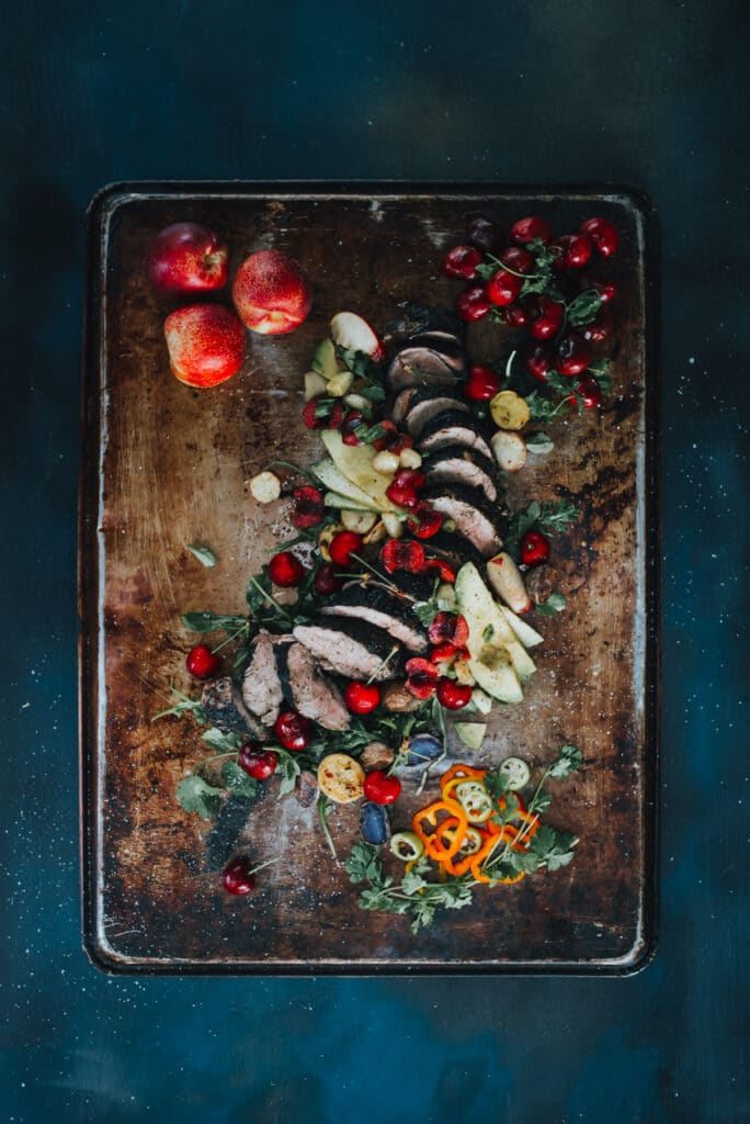 a truffle rubbed grilled pork tenderloin sliced thin with bright stone fruit salsa and garnish