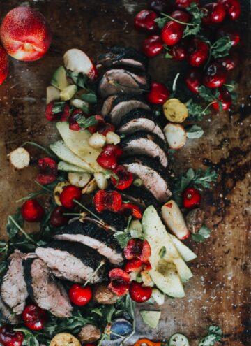 Close up of pork tenderloin with bright cherries and avocado slices