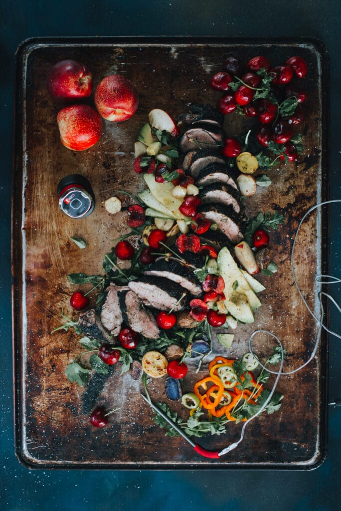 Above shot of a sliced grilled pork tenderloin topped with a fresh cherry and nectarine salsa with avocados and other various garnish