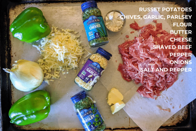 ingredients for philly cheesesteak baked potatoes. onions, peppers, herbs, cheese, butter, steak, flour