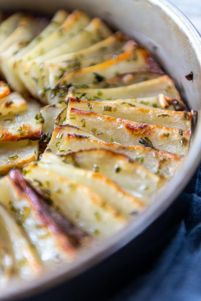 Perfectly browned edges of thin slices potatoes rolled in duck fat and baked