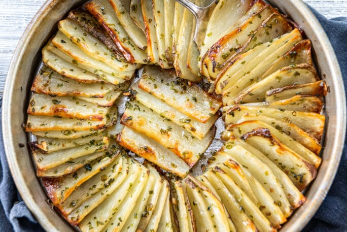 Layers of thin sliced potatoes - stacked like dominoes leaning on one another in a pan cooked til just crispy