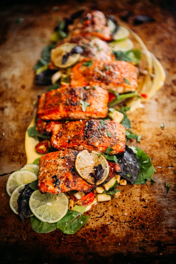 long shot of a salmon filet that has been portioned and grilled plated over greens with lime slices and thai basil as garnish