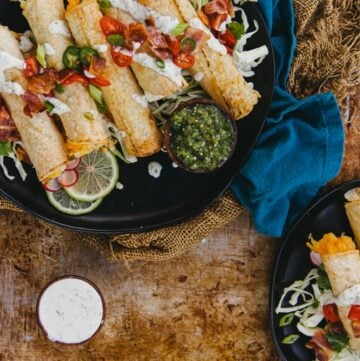 homemade air fryer potato stuffed taquitoes piled onto plated with a variety of toppings