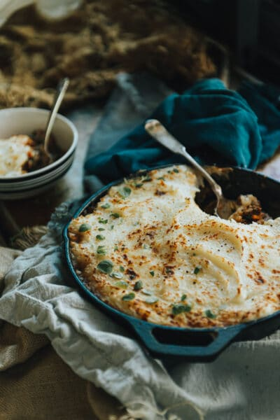 Creamy mashed potato topped shepherd's pie with Moroccan spices and a heaping portion taken out in a bowl on blue cloths