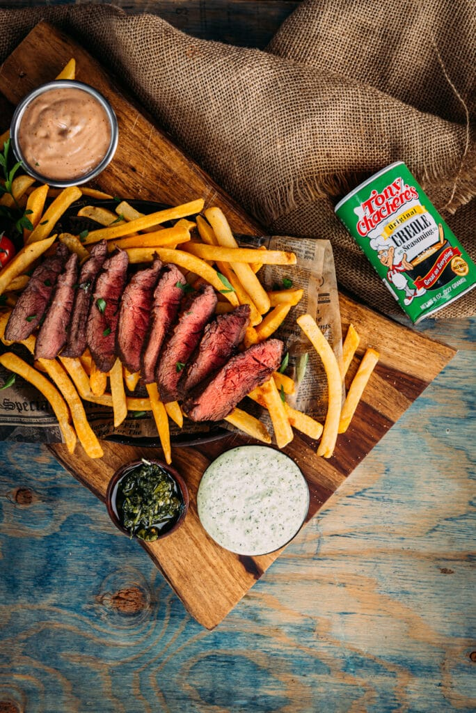 Over head shot of sliced flat iron steak with fries, dipping sauces on a wooden board