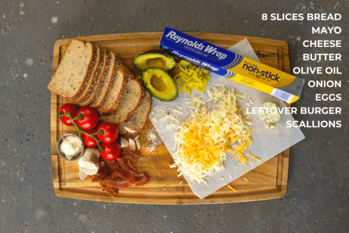 Ingredients to make the ultiamte grilled cheese, with shredded cheese, avocado, garlic, tomatoes and bread on a cutting board
