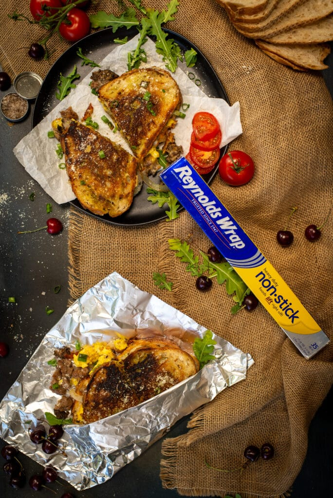 grilled cheese sandwiches on table with reynolds wrap foil, tomatoes and other ingredients