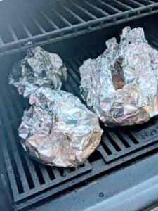 foil wrapped packets of pork bites on grill