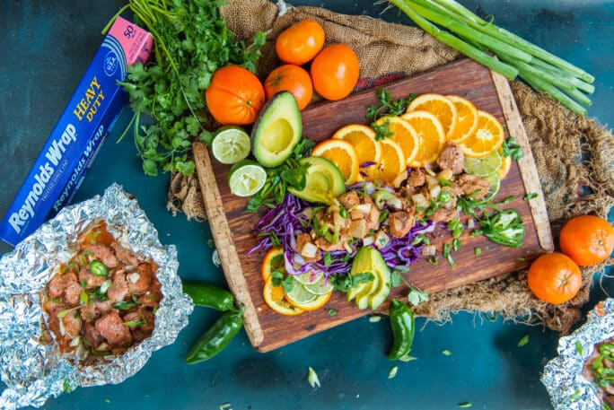 Flat lay of pork tenderloin bites over fresh sliced citrus with various fruit and cabbage garnish on cutting board and blue background.