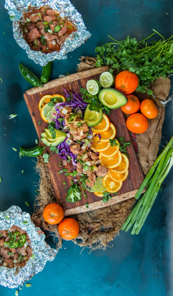 Pork tenderloin bites and shown in foil packets for ease of cooking on a blue background and cutting board with fresh citrus and other garnish