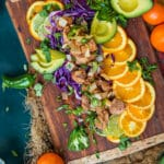 mojo pork bites over sliced citrus and chopped red cabbage on a cutting board