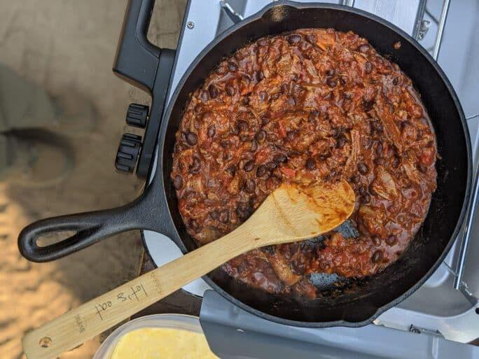 leftover pork chili being heated in cast iron on a camp stove
