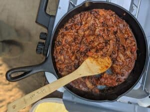 reheating pulled pork chili on camp stove in cast iron skillet