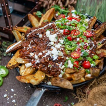 Crispy camping french fries in skillet topped with dutch oven chili