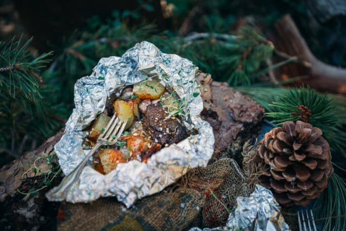 Opened foil wrapped steak and potatoes on log with fork