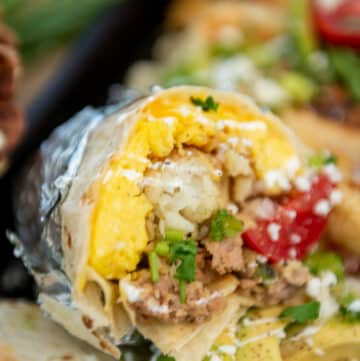 close up of make ahead burrito cooked, cut in half to show eggs, potatoes, and filling