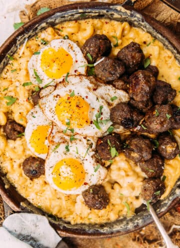 a skillet of macaroni and cheese with meatballs and fried eggs