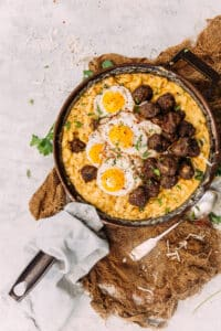 flat lay shot of a skillet filled with macaroni and cheese, topped with breakfast meatballs and fried eggs
