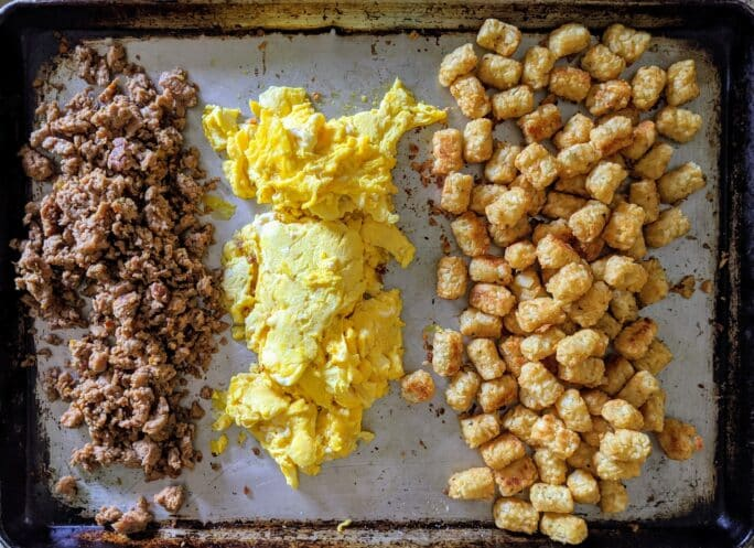 showing eggs, crispy tots, and sausage cooling on a sheet to fill burritos
