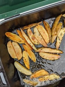 potato wedges cooking in oil on camp stove