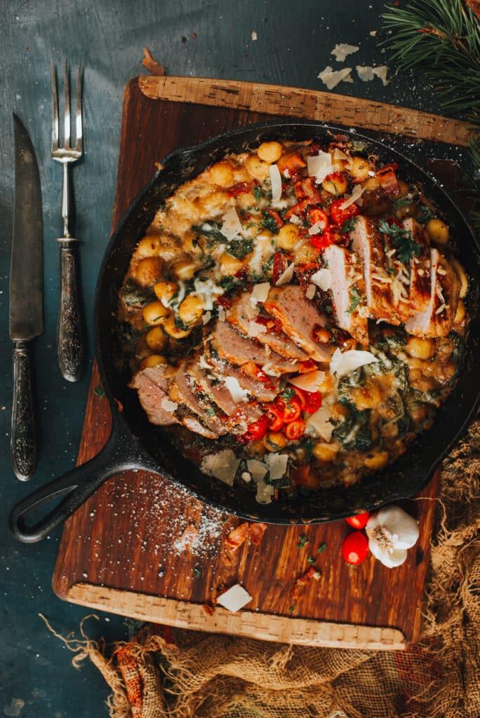 hearty pork tenderloin in cast iron skillet with cheesy gnochi