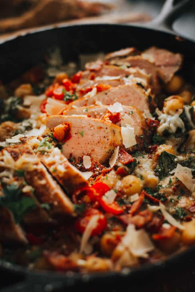 Close up of sliced pork tenderloin in skillet with gnocchi