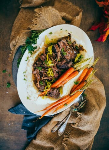 shredded mississippi pot roast on burlap served with mashed potatoes and roasted carrots