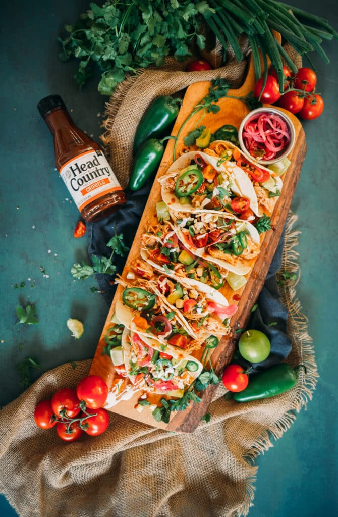 Multiple Instant Chipotle Chicken Tacos served in a wooden tray with salad
