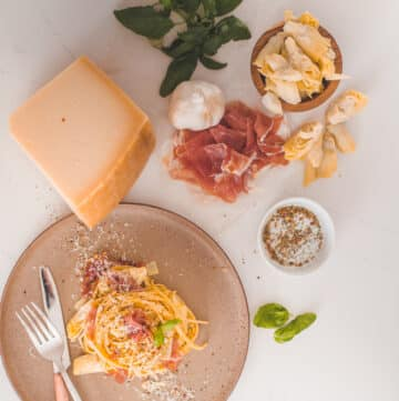 Flat lay ingredients for classic carbonara with a plate of finished pasta swirled with prosciutto and shaved cheese