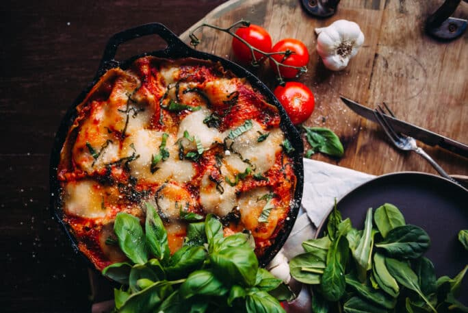 Cheesy Skillet Lasagna in a Table with Garlic, Cherry Tomato, Basil and Spinach