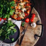 flat lay of the full skillet of lasagna with fresh ingredients to of garlic, basil and tomatoes