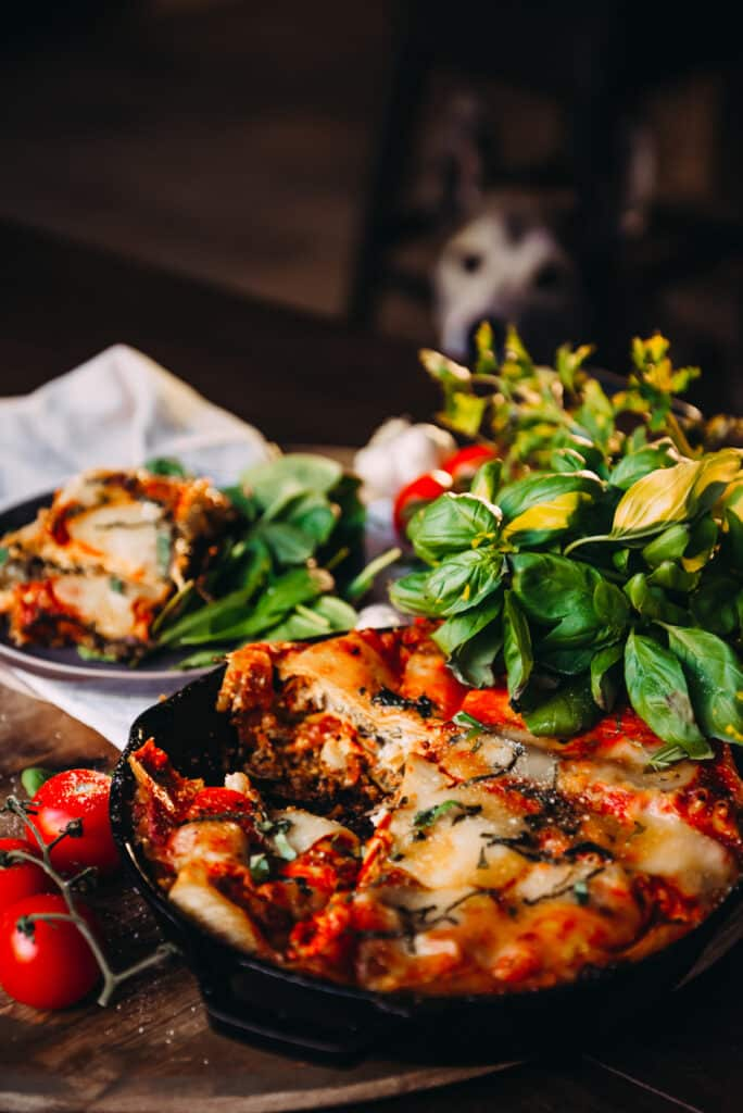 Freshly made Lasagna in Skillet with herbs and cherry tomatoes