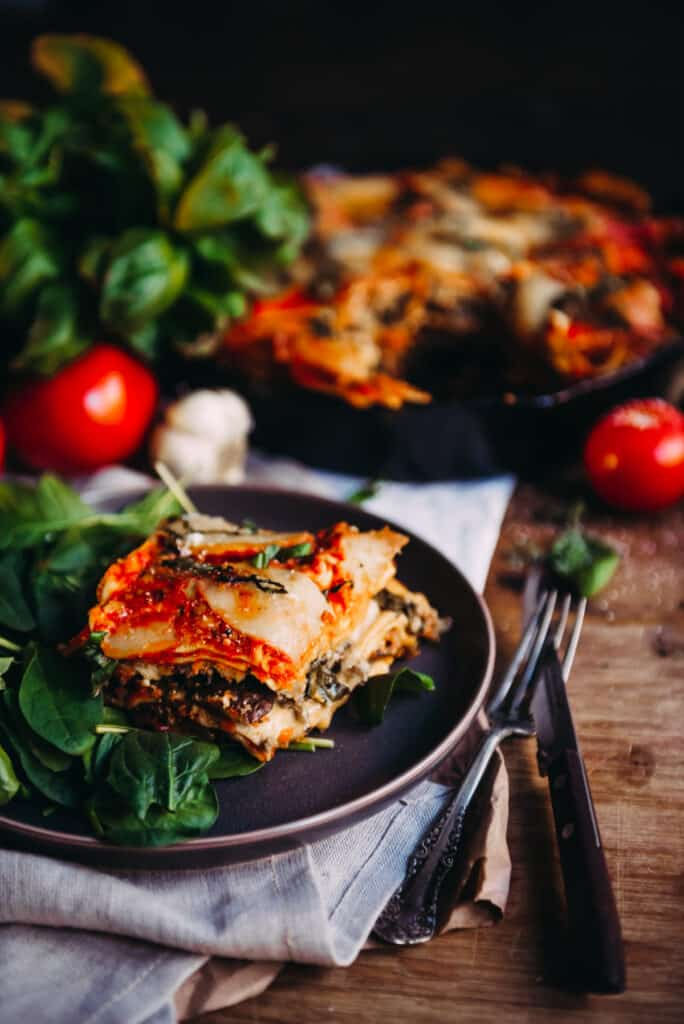 Half Sliced Lasagna in a Skillet with Spinach and Basil Leaves