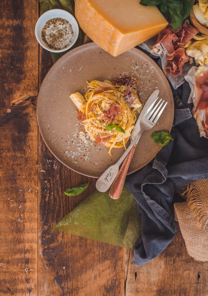 Classic Carbonara in a Plate along with Prosciutto and Grana Padano Cheese.