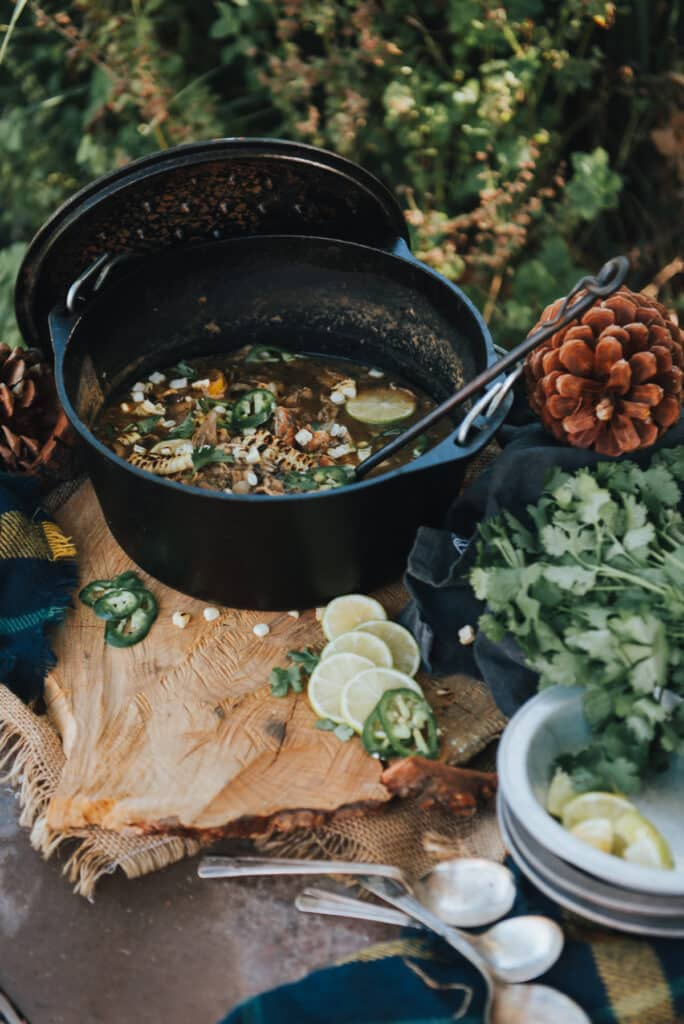 Showing white chicken chili in a Dutch oven outside in a woodland scene on a table with limes, jalapenos and avocados for topping