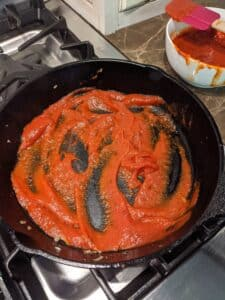 Skillet with marinara sauce spread over the bottom to start the lasagna layers