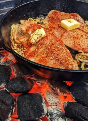Cooked tilapia in a cast iron pan over hot coals.