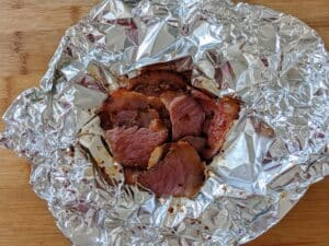 steamed pastrami in foil on cutting board ready to be served