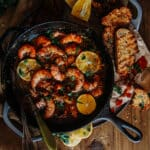 cast iron skillet filled with spicy sauce, jumbo shrimp, lemons and bread on the side for dipping