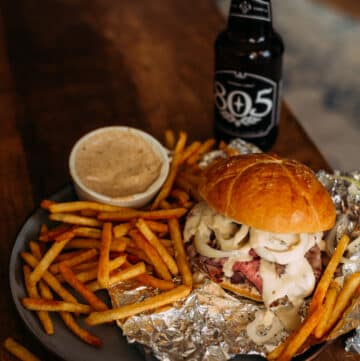 pit beef sandwich on plate with fries and a beer