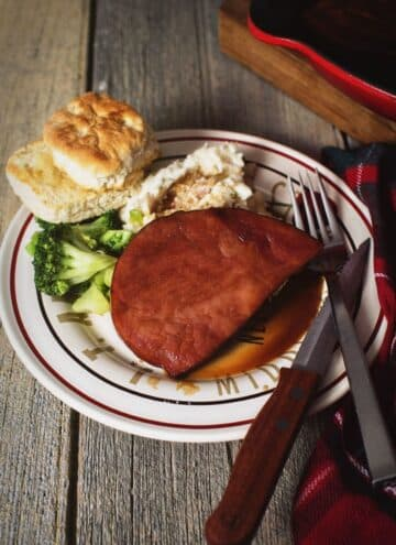 Cola ham steak on a white plate with a side of mashed potatoes, broccoli, and a biscuit.