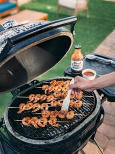 Shrimp on bamboo skewers on the grill being brushed with head co barbecue sauce