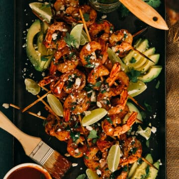 platter of bbq shrimp skewers grilled served with bbq sauce, over avocado slices, garnished with lime wedges, cotija and chimichurri
