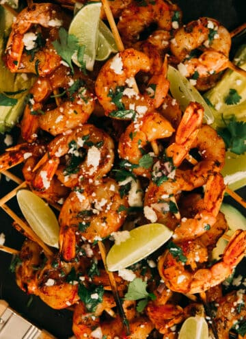 Bbq shrimp skewers on platter with crumbled cotija, brushed with chimichurri and lime wedges as garnish