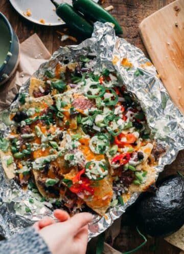 Carne asada nachos on a sheet of foil with a hand reaching in to grab a chip.